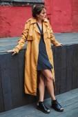 junge schöne Frau in orangefarbenem Trenchcoat und schwarzem Tupfen-Kleid, die verträumt beiseite schaut und die Zeit allein im alten Hof verbringt