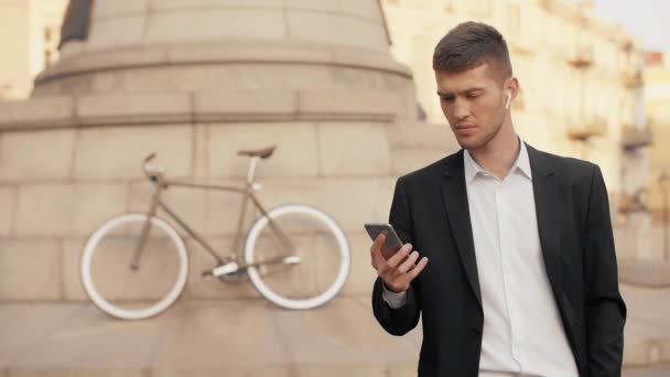 Young gloomy businessman in black suit seriously looking at the mobile phone screen and swiping across in the middle of a city square with a bicycle in the background and wireless headphones on