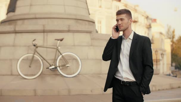 Young handsome businessman in black suit getting good news on the mobile phone holding hand in pocket standing in the middle of a city square with a bicycle and monument in the background