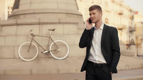 Fiatal jóképű üzletember üzleti megbeszélése a kezemet, zsebében kerékpár és egy emlékmű a háttérben a város tér mobiltelefon fekete öltöny
