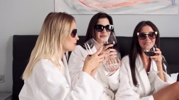 Követés ki lövés vonzó lányok, fehér fürdőköpeny és napszemüveg boldogan iszik vörösbor reggelivel az ágyban a szállodai szobában