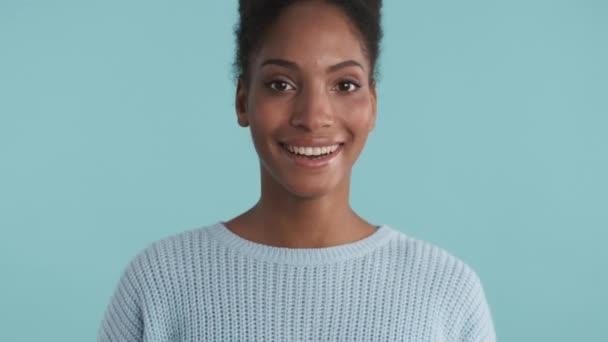 Portrét veselé africké americké dívky šťastně dívá do kamery přes modré pozadí