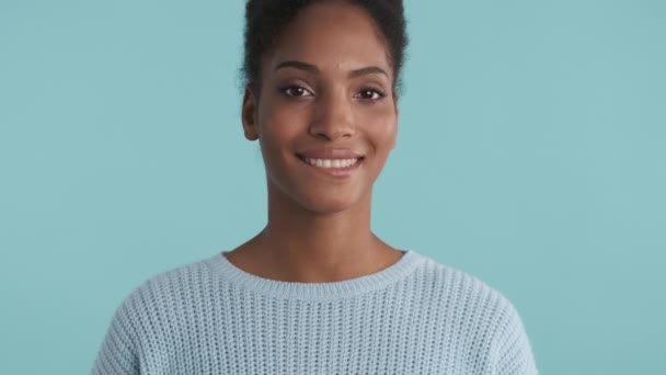 Portrait of pretty flirty african american girl dreamily looking in camera over blue background