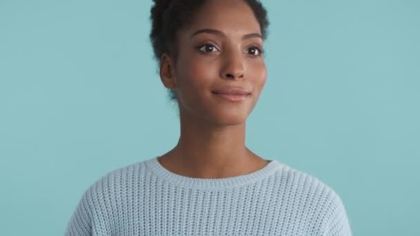 Portrét usmívající se africké americké dívky radostně dívá do kamery přes modré pozadí