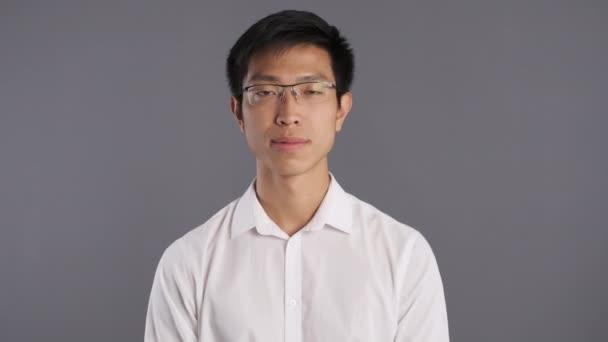 Mladý pohledný asijský muž v brýlích šťastně ukazuje v pořádku gesto na kameře přes šedé pozadí
