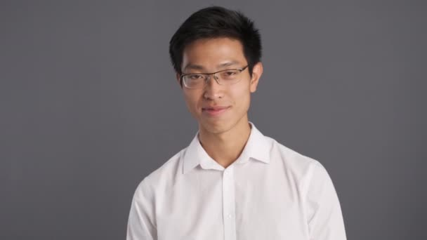 Young confident asian man in eyeglasses rejoicing on camera over gray background. Glad expression