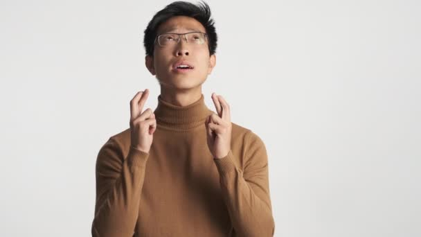 Young worried asian man in eyeglasses crossed fingers with hope making wish isolated. Please expression