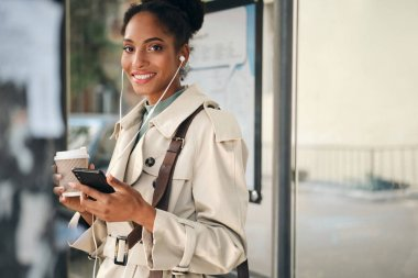Beautiful casual African American girl in stylish trench coat with coffee to go and cellphone joyfully looking in camera at bus stop