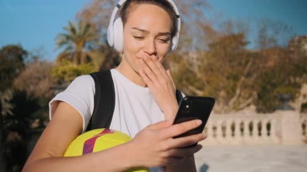 Krásná usměvavá dívka ve sluchátkách s fotbalovým chichotáním a baví pomocí smartphonu na ulici. Atraktivní sportovní dívka s batohem vesele pomocí mobilní aplikace venkovní