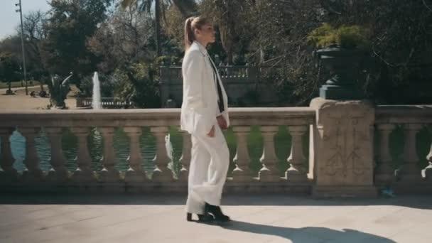 Seitenansicht einer attraktiven eleganten Frau im weißen Anzug, die selbstbewusst durch den alten Stadtpark geht