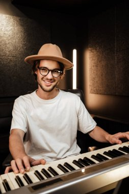 Young stylish music arranger composing song on midi piano in recording studio. Attractive guy happily playing on electric piano in studio