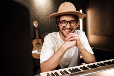 Young attractive musician joyfully working on new music album in modern sound recording studio