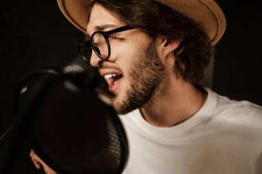 Close up handsome male musician emotionally singing in microphone recording song in professional studio