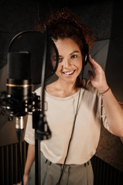 Pretty female singer in headphones happily looking in camera working on new music album in sound recording studio