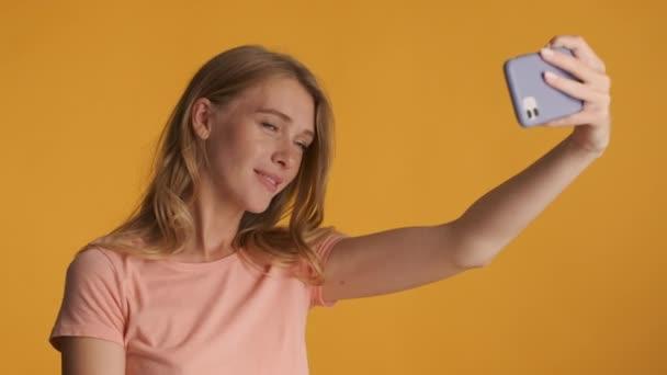 Gyönyörű érzéki szőke lány csinál szelfi okostelefon felett színes háttér