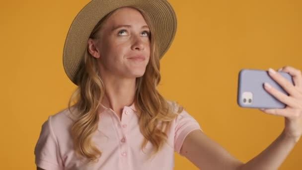 Gyönyörű, elegáns, szőke lány kalapban vidáman rögzíti a videót okostelefonon, színes háttérrel. Modern szépségblogger