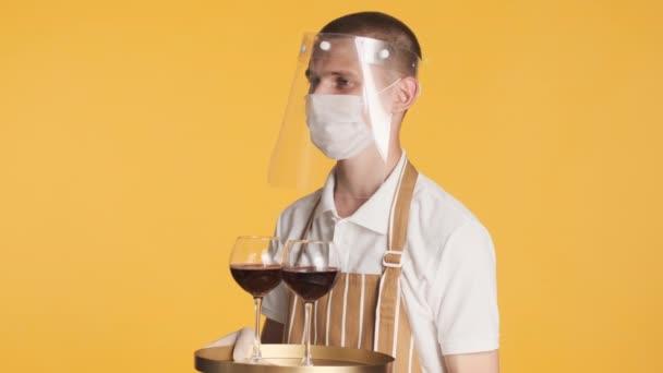 Mladý číšník v lékařských a ochranných maskách, podnos s červeným vínem na barevném pozadí. Bezpečnostní koncepce