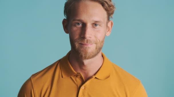 Attraktiver blonder bärtiger Mann posiert selbstbewusst vor der Kamera vor buntem Hintergrund
