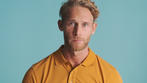 Young blond bearded man uncertainly looking in camera and showing i dont know expression over colorful background