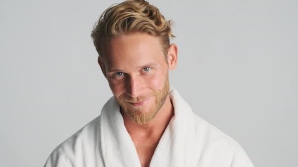 Hezký jistý blond vousatý muž v županu šťastně pózuje na kameře přes bílé pozadí