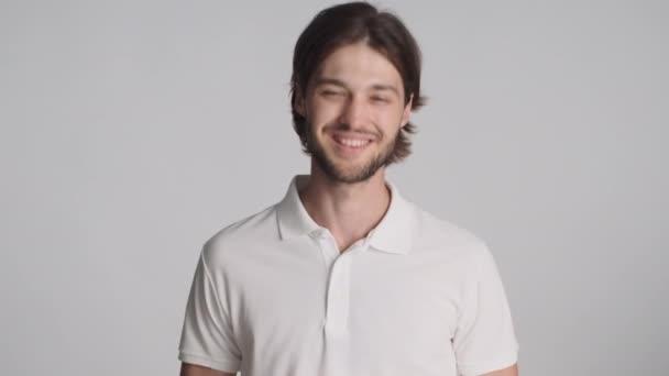 Atraktivní veselý muž šťastně hledící do kamery a mávající ano gestem přes bílé pozadí. Souhlasný výraz