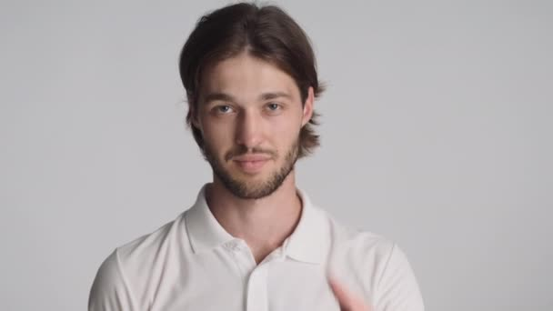 Attractive cool guy happily showing see you later gesture on camera over white background. Agree expression