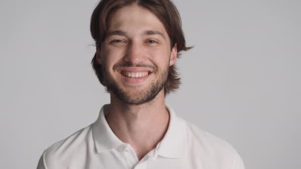 Zblízka hezký veselý chlap šťastně dívá do kamery a kývnout na šedém pozadí