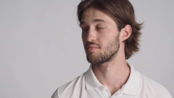 Zblízka mladý pohledný muž sebevědomě dívá stranou na kopírovat prostor a ve fotoaparátu přes bílé pozadí.