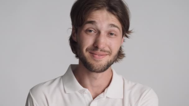 Portrét atraktivní veselý chlap šťastně dívá do kamery přes bílé pozadí
