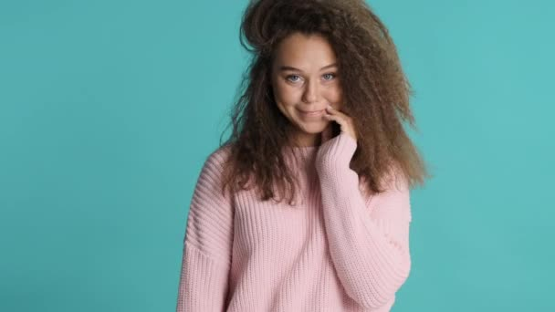 Pretty smiling brunette girl with her fluffy wearing pink sweater charmingly posing on camera over colorful background