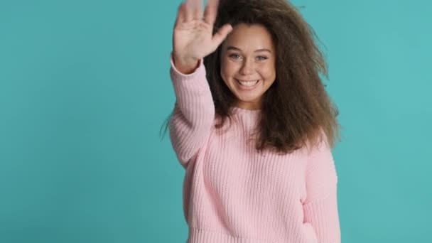 Beautiful smiling brunette girl wearing sweater happily waving hello to friend isolated on blue background. Greeting expression