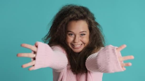 Roztomilá brunetka dívka šťastně roztáhnout ruce a obejmout na kameru přes modré pozadí. Pojď ke mně, chci tě obejmout.