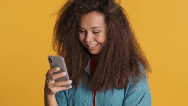 Csinos barna lány boldogan ellenőrzi kapott értesítést okostelefonon keresztül színes háttér. Modern technológiai koncepció