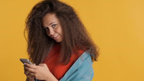 Docela pozitivní brunetka dívka dívá do kamery a usmívá chatování s přítelem na smartphone izolované na žlutém pozadí