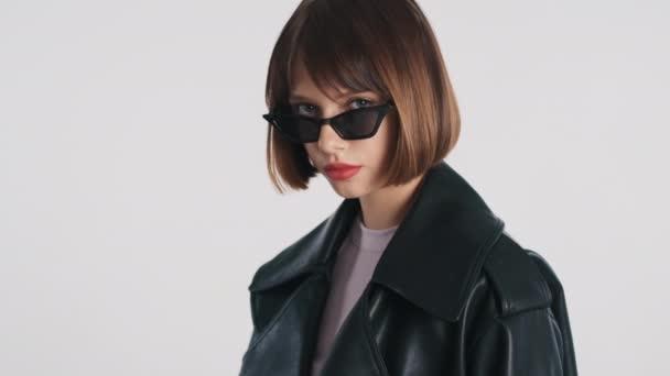 Gyönyörű elegáns barna lány Bob haj napszemüvegben öltözött alkalmi kopás néz magabiztosan elszigetelt fehér háttérrel. Divatlány