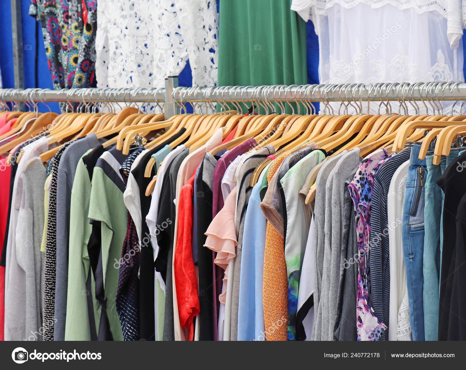 306c44ba3680 Στοίβα από πολύχρωμα ρούχα στις ξύλινες κρεμάστρες που πωλούνται στην αγορά  — Εικόνα από ...
