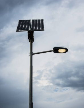 Solar panel on street lamp post with light on and cloudy sky.