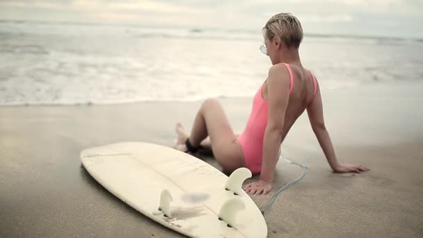 Blonde girl with surfboard on beach