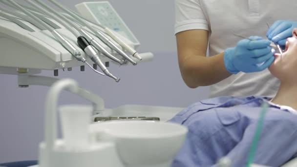 Hezké ženské zuby zkoumáním na zubní klinice