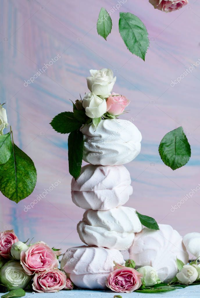 Delicious and airy marshmallows with buds of roses and leaves on the table