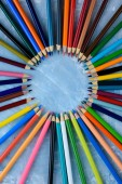 Multicolored pencils for creative work on a wooden background.