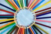 Barevné tužky pro kreativní práci na dřevěné pozadí