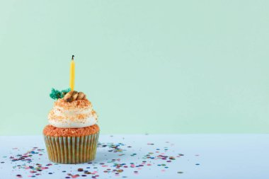 One cupcake with a candle on a neon mint background