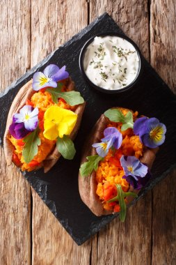 Delicious baked sweet potato with cream cheese decorated with ed