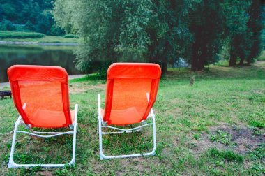 Two orange chaise longues by Elbe river