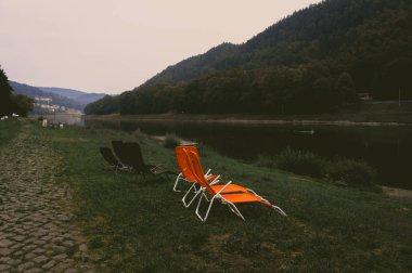 Black and orange sun loungers on Elbe river bank at twilight, Saxon Switzerland, Germany