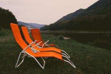 Orange sun loungers on Elbe river bank at twilight, Saxon Switzerland, Germany
