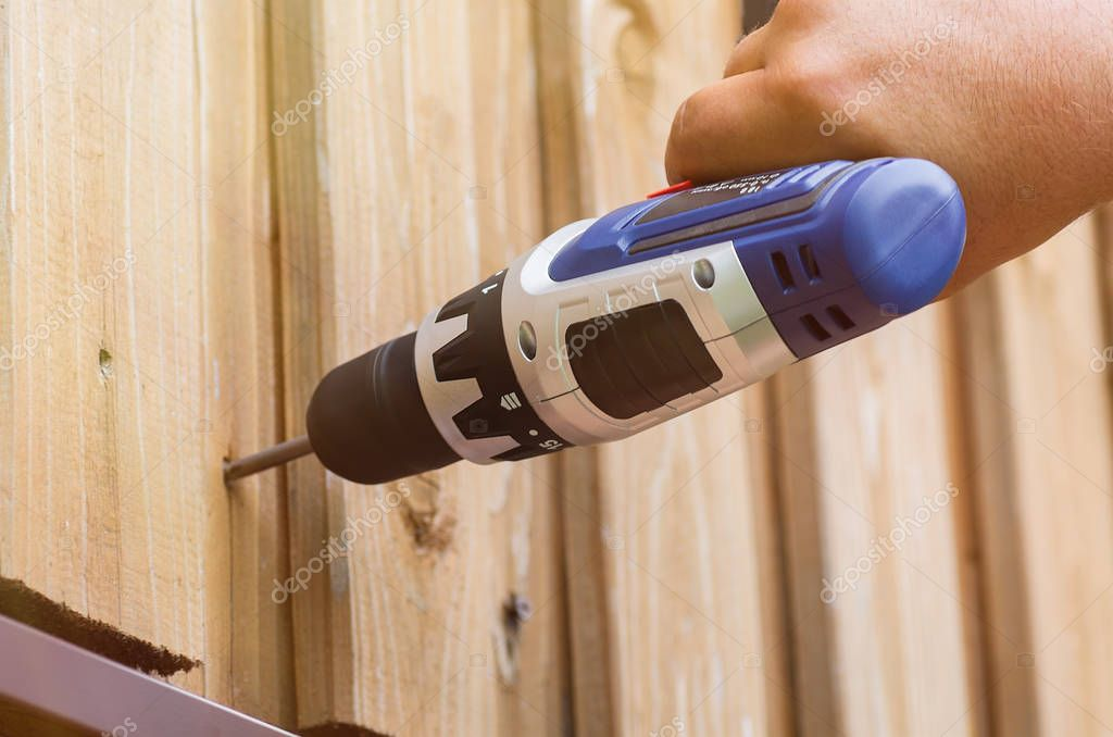 Electric screwdriver in hand. Closeup of worker. Work with a tree. Construction of a wooden house.