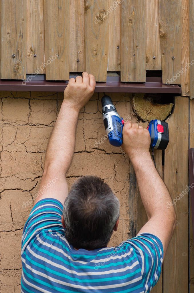 The person is engaged in construction with the help of an electric screwdriver - works on the spot with the help of a hand tool. Construction works.