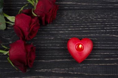 Red roses and a red heart-shaped candle on a black wooden background as the Valentine day or love concept stock vector